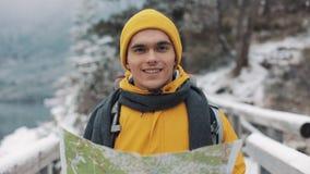 Hombre atractivo joven que lleva el mapa amarillo de la tenencia de la ropa del invierno y que mira en la cámara Retrato de un tu almacen de video