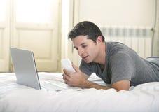 Hombre atractivo joven que miente en cama o el sofá usando el ordenador portátil del teléfono móvil y del ordenador que trabaja d Imagenes de archivo
