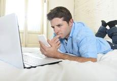 Hombre atractivo joven que miente en cama usando el teléfono móvil y el ordenador portátil que trabajan de hogar Fotografía de archivo libre de regalías