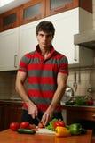 Hombre atractivo joven que prepara la ensalada Fotografía de archivo libre de regalías