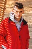 Hombre atractivo joven que presenta en la chaqueta roja cubierta con hermoso Imágenes de archivo libres de regalías
