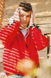 Hombre atractivo joven que presenta en la chaqueta roja cubierta con hermoso Fotografía de archivo libre de regalías