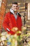 Hombre atractivo joven que presenta en la chaqueta roja cubierta con hermoso Imagen de archivo libre de regalías