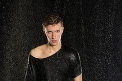 Hombre atractivo joven que se coloca debajo de la lluvia en camiseta Fotografía de archivo