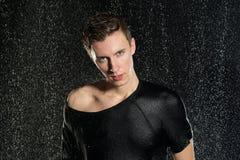 Hombre atractivo joven que se coloca debajo de la lluvia en camiseta Foto de archivo libre de regalías