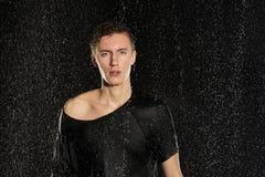 Hombre atractivo joven que se coloca debajo de la lluvia en camiseta Imágenes de archivo libres de regalías