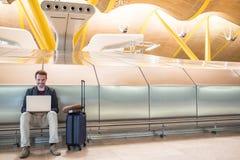 Hombre atractivo joven que se sienta en el aeropuerto que trabaja con un lapto imagenes de archivo