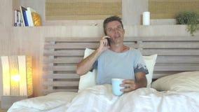 Hombre atractivo joven 30s con los ojos azules felices y relajados en casa en cama que habla con la sonrisa del teléfono móvil