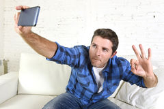 Hombre atractivo joven 30s que toma la imagen del selfie o el vídeo del uno mismo con el teléfono móvil en casa que se sienta en  Fotografía de archivo