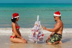 Hombre atractivo Papá Noel de la muchacha en un abeto de la playa Foto de archivo libre de regalías