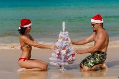 Hombre atractivo Papá Noel de la muchacha en un abeto de la playa Foto de archivo