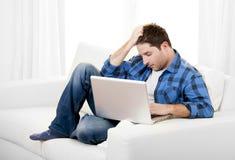 Hombre atractivo preocupante con el ordenador que se sienta en el sofá Fotografía de archivo libre de regalías