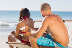 Hombre atractivo que aplica la crema del sol en sus novias detrás Foto de archivo