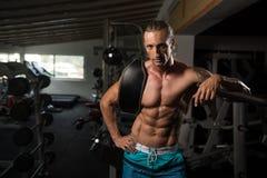 Hombre atractivo que descansa en el ejercicio de Afther del gimnasio Imagen de archivo libre de regalías