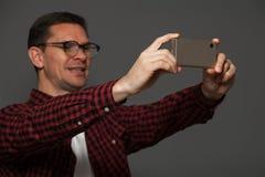 Hombre atractivo que hace el selfie en smartphone Imagenes de archivo