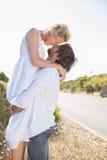 Hombre atractivo que levanta encima de su novia bonita foto de archivo