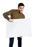 Hombre atractivo que muestra y que señala la cartelera en blanco Foto de archivo