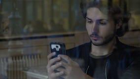 Hombre atractivo que pasa tiempo en medios sociales del smartphone mientras que espera a amigos en restaurante almacen de video