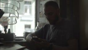 Hombre atractivo que se sienta cerca de la ventana en café y que sostiene el smartphone, usando la tecnología inalámbrica almacen de video