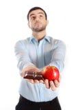 Hombre atractivo que sostiene el chocolate y Apple Foto de archivo libre de regalías