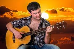 Hombre atractivo que toca la guitarra en la puesta del sol Imagen de archivo