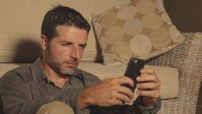 Hombre atractivo y hermoso joven que se sienta en el piso de la sala de estar enfocado y concentrado usando establecimiento de un almacen de video