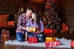Hombre atractivo y mujer alegres que se sientan cerca del abrazo del árbol de navidad pares que abrazan cerca del árbol de navida fotografía de archivo