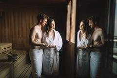 Hombre atractivo y mujer hermosa que se relajan junto en sauna foto de archivo