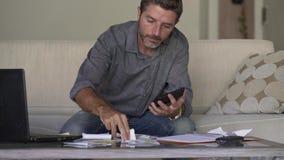 Hombre atractivo y ocupado joven en los costos del sofá del sofá de la sala de estar y los pagos mensuales de la deuda que consid almacen de metraje de vídeo