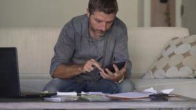 Hombre atractivo y ocupado joven en los costos del sofá del sofá de la sala de estar y los pagos mensuales de la deuda que consid almacen de video