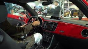 Hombre auto de la exposición que prueba el coche de Volkswagen y su tablero de instrumentos dentro del coche almacen de metraje de vídeo