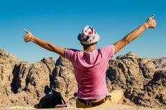 Hombre autosatisfecho en sombrero en la montaña superior con los pulgares para arriba No abandone el concepto de la motivación Go Fotografía de archivo