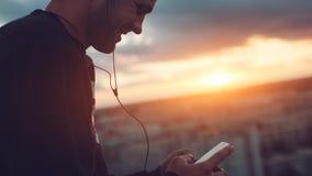 Hombre aventurado con música que escucha del smartphone en el top del tejado en la puesta del sol fotografía de archivo