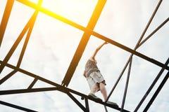Hombre aventurado joven que equilibra en el top del puente del alto metal fotografía de archivo