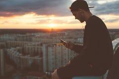 Hombre aventurado que se enfría al borde del tejado en la puesta del sol fotografía de archivo