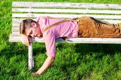 Hombre bávaro rubio que duerme al aire libre en un banco fotos de archivo libres de regalías
