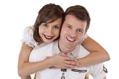 Hombre bávaro sonriente feliz en mujer que lleva del amor Fotografía de archivo
