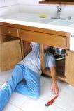 Hombre bajo el fregadero que alcanza para la llave Imagenes de archivo