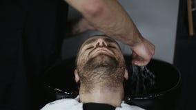 Hombre Barber Washing Male Hair en una barbería almacen de video