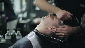 Hombre Barber Washing Male Hair en una barbería metrajes