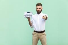 Hombre barbudo adulto joven, señalando en la cámara y sosteniendo una caja de regalo Foto de archivo