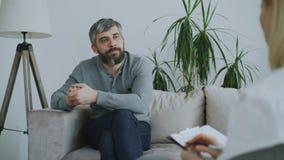 Hombre barbudo adulto que se sienta en el sofá que habla con el psicoterapeuta de sexo femenino en oficina dentro almacen de video