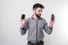 Hombre barbudo aislado en un fondo ligero que sostiene un smartphone moderno y un teléfono celular viejo con los botones Imagenes de archivo