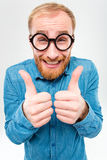 Hombre barbudo alegre divertido en los vidrios redondos que muestran los pulgares para arriba Imagenes de archivo
