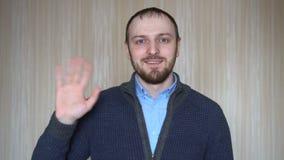 Hombre barbudo amistoso que agita con su mano, socios comerciales de granizada en el encuentro metrajes