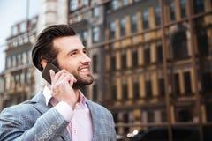 Hombre barbudo atractivo en chaqueta que habla en el teléfono móvil Imagen de archivo