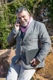 Hombre barbudo atractivo en el campo con el teléfono y la tableta Imagenes de archivo