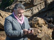 Hombre barbudo atractivo en la costa que habla en el teléfono Fotos de archivo libres de regalías
