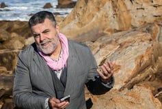Hombre barbudo atractivo en la costa que habla en el teléfono Imagenes de archivo