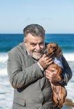 Hombre barbudo atractivo en la playa con el perro basset rojo Fotografía de archivo